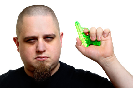 A menacing man holds a water pistol.